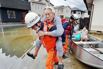 九州北部を襲った大雨で浸水した自宅から救助される男性ら(8月29日、佐賀県大町町)