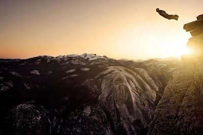 日の出とともに、カリフォルニア州ヨセミテ国立公園のハーフドームから飛び降りるウイングスーツ・ベースジャンパー。ヨセミテ国立公園では、ベースジャンプは全面的に禁止されている。2015~2016年以降、ウイングスーツ・ベースジャンプの死者数は減少している(PHOTOGRAPH BY CHRISTIAN ADAM, CAVAN IMAGES)
