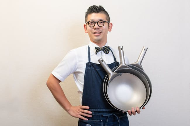 台所番長こと、合羽橋の老舗料理道具店、飯田屋の6代目、飯田結太氏。今、プロが注目しているチタン製の中華鍋は、サイズ違いを3つ重ねているのに片手で軽々持てるほど軽い