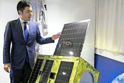 実証実験用の衛星模型を前に語る岡田光信アストロスケールCEO