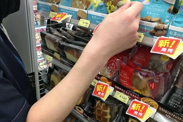 「新発売」の札が顧客の目をひくコンビニのスイーツ棚(東京都港区)