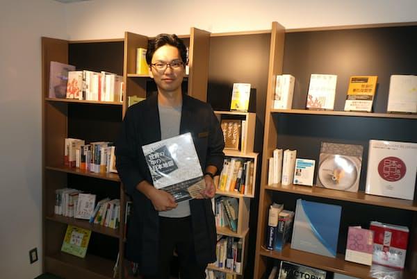 一見、お互いに無関係の本が並ぶ書棚の前で展示方法を解説する伊藤晃氏