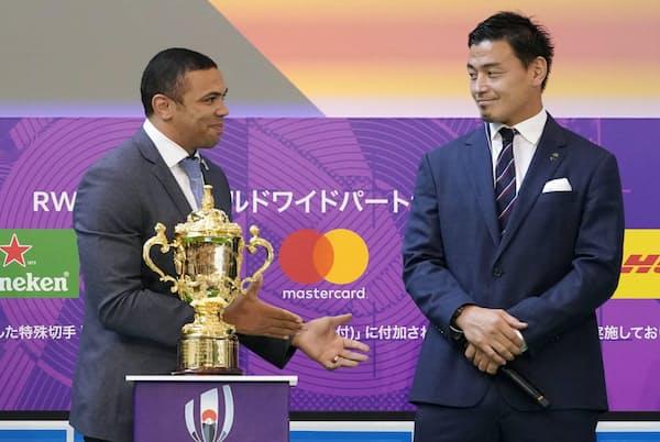 ラグビーW杯日本大会の開幕100日前を祝うイベントに出席した五郎丸歩選手。レジメンタルタイがよく似合う。左は元南アフリカ代表のブライアン・ハバナさん(19年6月12日、東京都千代田区)=共同
