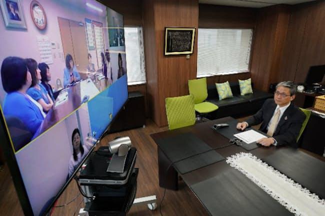 地方の女性幹部とテレビ会議をする新日本科学の永田会長兼社長(東京都中央区)