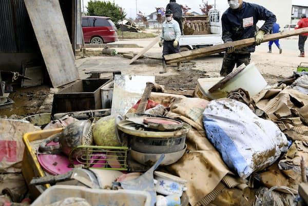 浸水被害のあった住宅の災害ごみを運ぶボランティア(10月21日午後、長野市)=共同