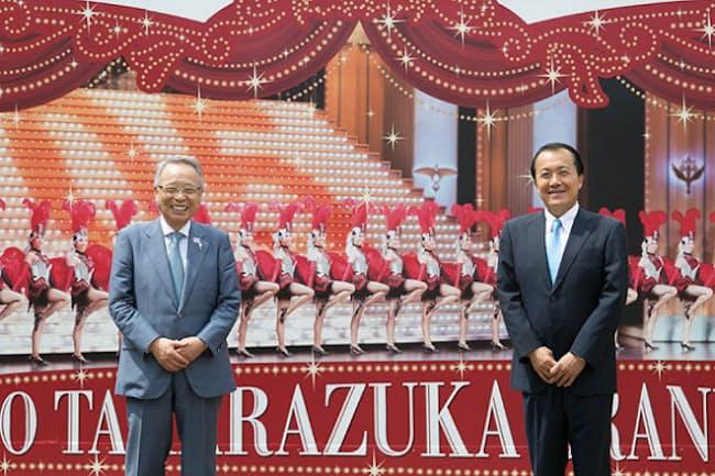 宝塚大劇場(兵庫県宝塚市)の正門すぐにあるレビューの大看板の前で。豊島区高野区長(左)と宝塚歌劇団小川理事長