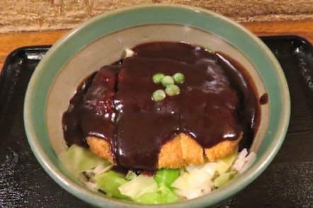 黒褐色のこってりしたソースをかけた味司野村のドミグラスソースカツ丼