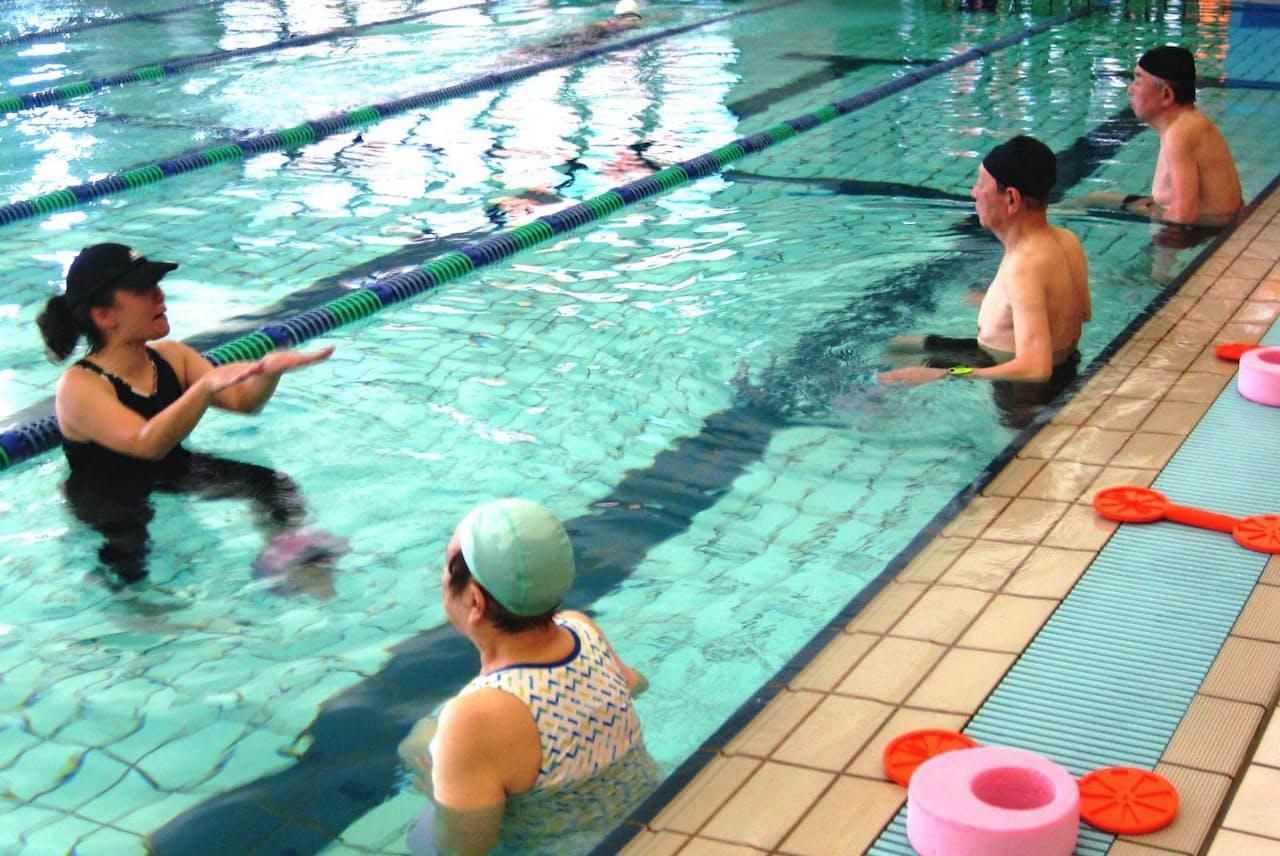 インストラクター(左)の掛け声に合わせて水中で体を動かす高齢者(埼玉県蕨市の「ルネサンス蕨24」)