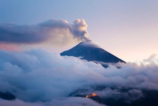 薄明かりの中、噴煙を上げるエクアドルのトゥングラワ火山。火山噴火は、地球が内部に蓄えた炭素を表面に戻す方法の1つだ(PHOTOGRAPH BY MIKE THEISS, NAT GEO IMAGE COLLECTION)