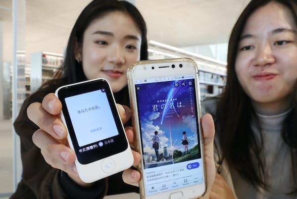 台湾からの留学生に教えてもらった好きなアニメをポケトーク(左)で翻訳すると「あなたの名前。」。日本語題名は「君の名は。」(東京都文京区の日本女子大)=三浦秀行撮影