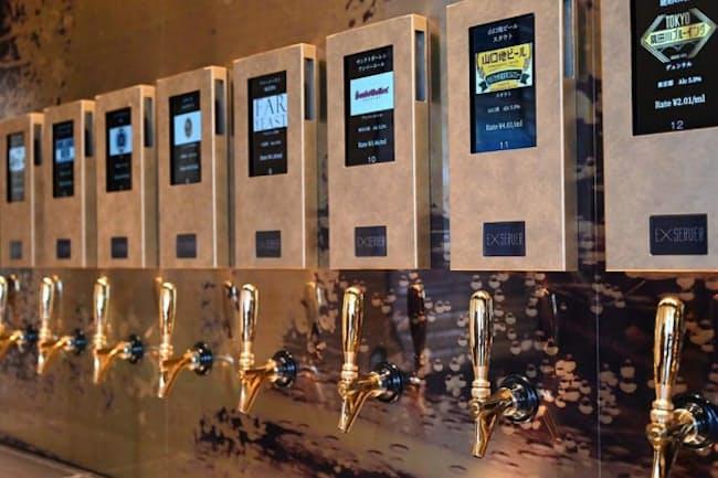 タイトーが東京・銀座にオープンした「EXBAR TOKYO」。壁にはビールサーバーがずらりと並ぶ(写真:酒井康治、以下同)