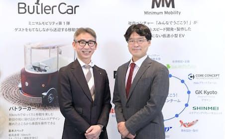 ローランド・ベルガーの長島聡社長(左)と慶応義塾大学の田中浩也・教授(右)。ローランド・ベルガーが東京モーターショーで展示した「バトラーカー」のポスターを背景に撮影