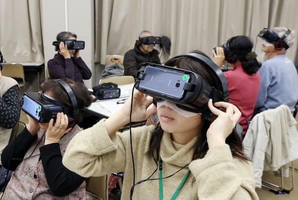 認知症の人がどう見えているかをVRで体験する参加者(2019年12月、神戸市)