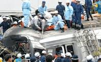 脱線しマンションに激突したJR福知山線の車両で救助活動する消防隊員ら(2005年4月25日、兵庫県尼崎市)