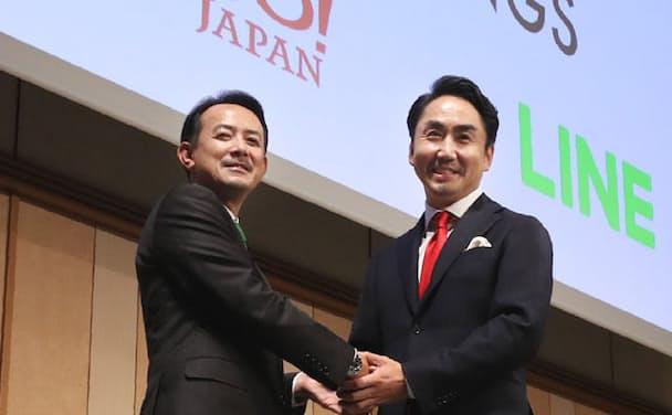 経営統合の記者会見で握手するZホールディングスの川辺健太郎社長(左)とLINEの出沢剛社長(右)、2019年11月18日、東京都港区で撮影