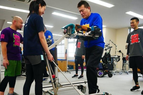 トレーナーらの補助のもと、専用の歩行器を使ってジムの中を歩く上野さん(東京・江東)