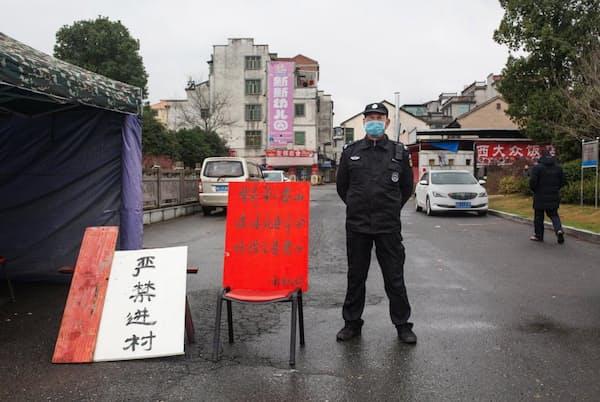 新型コロナウイルスが発生した武漢から580キロ離れた浙江省永康市。外部の人間が入らないように、村へ通じる道路を警備する村人。赤い板には「人の命は泰山よりも重い。感染が拡大すれば命令を下す。予防と管理は責任」と書かれている(PHOTOGRAPH BY ROBAN WANG, NATIONAL GEOGRAPHIC)