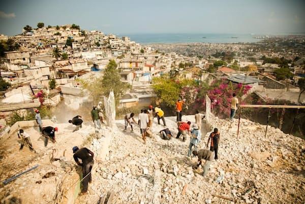 マグニチュード7.0の地震がハイチの首都を襲った2010年1月12日の翌日、少女の手当をする救急隊員。瓦礫は撤去されたものの、ハイチの経済状況は依然として厳しく、国民の3人にひとりが緊急の食糧援助を必要としている(PHOTOGRAPH BY EDUARDO MUNOZ, REUTERS)