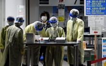 韓国からの便で成田空港に到着する乗客を待つ検疫官ら(3月上旬)