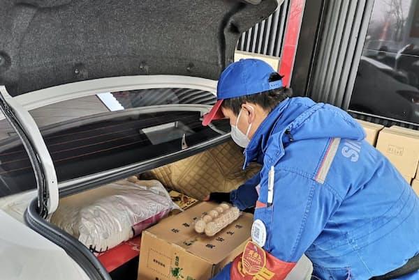ガソリンスタンドの従業員が車のトランクに野菜を積んでくれる
