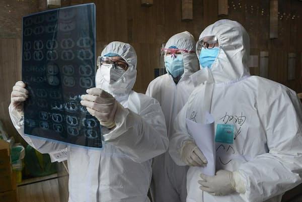 中国、湖北省孝感市雲夢県の病院で、肺のCT画像を確認する医師たち(PHOTOGRAPH BY STR/AFP/CHINA OUT VIA GETTY IMAGES)