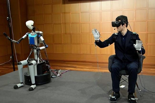 東京大学などが開発した分身ロボット「テレサ6」(左)と操作者