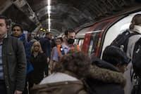 2020年3月3日、英ロンドン地下鉄。乗客が車両に乗り込む中、駅員はマスクを装着している(PHOTOGRAPH BY BRYN COLTON, BLOOMBERG/GETTY IMAGES)