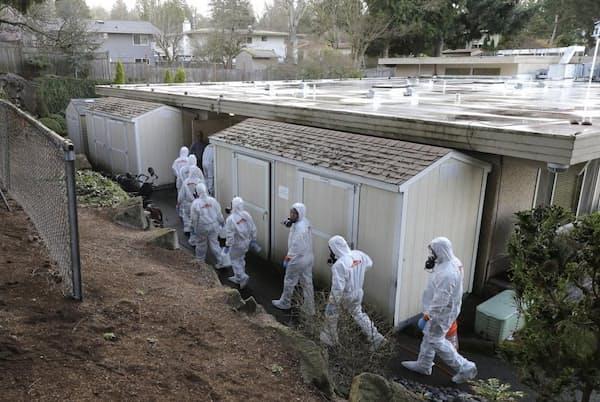 2020年3月11日水曜日、防護服と保護マスクに身を包んでシアトル近郊の街カークランドのライフケア・センターに入り、清掃と消毒を行うサーブプロ社(災害後の清掃や修復を手掛ける企業)の作業員。この介護施設は、米ワシントン州の新型コロナウイルス集団発生の中心地となった(PHOTOGRAPH BY TED S. WARREN, AP IMAGES)