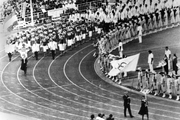1980年モスクワ五輪の開会式で、英国チームの代表として五輪の旗を持つ英国オリンピック委員会事務総長のディック・パルマー氏(右手前の男性)。ソビエト連邦がアフガニスタンに侵攻したことを受け、英国の選手は開会式をボイコットした(PHOTOGRAPH FROM AP)