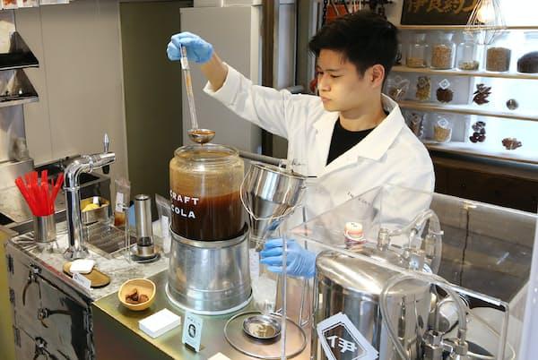 10種類以上のスパイスが入った原液に炭酸水などを加えてクラフトコーラを作る(東京都新宿区の伊良コーラ)=三浦秀行撮影