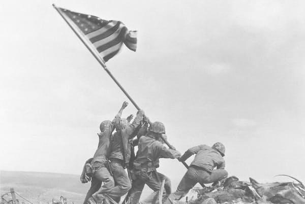 1945年2月23日、5日間の激しい戦いを終え、硫黄島の最高峰に星条旗を掲げる米海兵隊員たち。ジョー・ローゼンタールが撮影したこの写真は全米で高く評価され、同年、ピュリツァー賞に輝いた(PHOTOGRAPH BY JOE ROSENTHAL, AP)