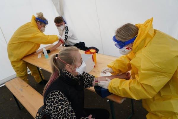 2020年3月27日、ベルリンの診療所脇のテントで、新型コロナらしい症状のある人から血液を採取する医療ボランティアたち。ロックダウン下の人々が仕事に戻れるようにし、打撃を受けた経済を再始動させるため、ドイツ政府は4月末までに1日20万件の検査ができる体制を整えようとしている(PHOTOGRAPH BY SEAN GALLUP, GETTY IMAGES)