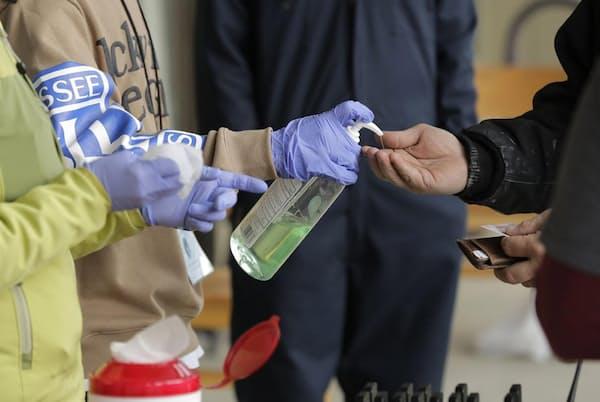2020年3月27日、米国ワシントン州オリンピアのクリニック。オピオイド依存症の治療薬を受け取りに来た人々が、アルコール消毒液を手に受ける。クリニックは現在、屋外で患者を受け入れている。新型コロナウイルス感染症が流行している間は、感染防止対策の一環として来院回数を減らすため、薬の処方期間の延長が認められた(Photograph by Ted S. Warren, AP Photo)