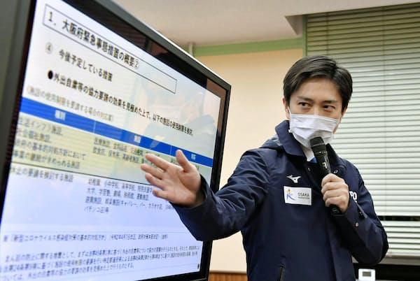 4月7日夜、記者会見する大阪府の吉村洋文知事=共同
