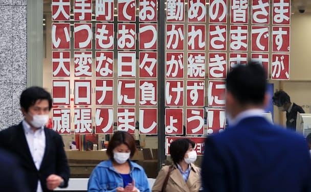 オフィス街には「コロナに負けるな」との張り紙も(東京・大手町)