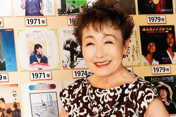歴代のアルバムジャケットの前で歌手人生の思い出を語る加藤登紀子さん