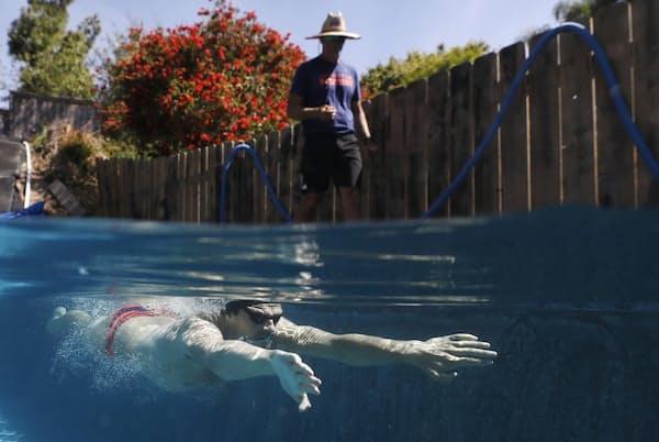 オリンピック米国代表のマイケル・アンドリュー選手は、カリフォルニア州サンディエゴにある自宅のプールで、父親の指導を受けながら訓練を続けている。今年は、新型コロナウイルス感染症のパンデミックにより、トップアスリートから、純粋に水泳を楽しみたい一般人まで、これまでとは全く違う夏を迎えようとしている(PHOTOGRAPH BY SEAN M. HAFFEY, GETTY IMAGES)