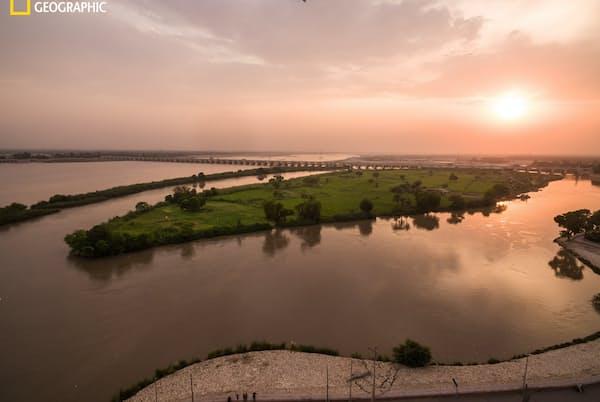 険しい山々を下った氷河の融解水は、パキスタンのシンド州の平野で堂々たる大河になる。奥に見えるサッカル堰(せき)は植民地時代に建設されたもの。インダス川の水を運河網に流して砂漠に送り、綿花や小麦、米の生産を可能にした。旧宗主国の英国が築いたこの灌漑(かんがい)システムは、今でも世界最大級を誇る(PHOTOGRAH BY BRENDAN HOFFMAN)