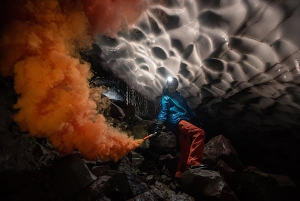 セントへレンズ山の火口に形成されたモスラ洞窟内で、発煙筒を点火するドイツ、ルール大学の科学者アンドレアス・フリッチ氏。その煙で、噴気孔から出る高温ガスがどのように洞窟を削り取ったかを調べることができる(PHOTOGRAPH BY ERIC GUTH)