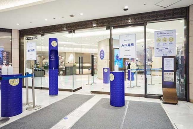 2020年5月30日の営業再開後、入り口を3つに制限した伊勢丹 新宿店。既存の入り口のデザインと合わせるため、新たに消毒液を置く専用の台などに統一感を持たせた。ブルーは伊勢丹のロゴの色だ