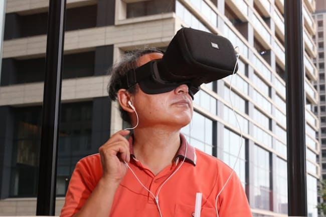 ゴーグル、スマホ、イヤホンがあればライブを仮想現実(VR)で楽しめる(東京・大手町)=三浦秀行撮影