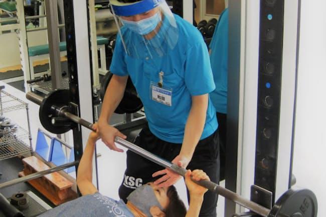 スタッフの和田亮一さんの指導を受けながら、バーベルを持ち上げる大森貞子さん(千葉県勝浦市の勝浦スポーツクラブ)