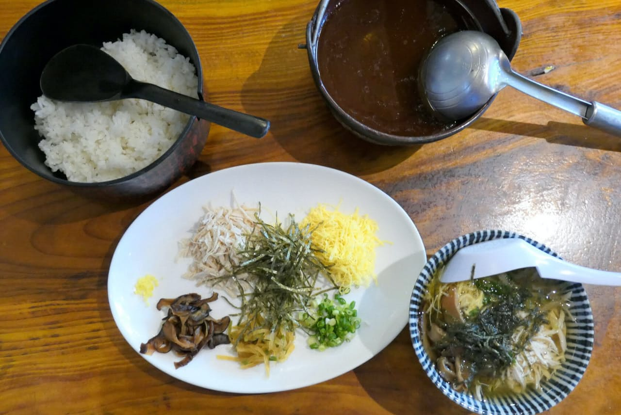 ご飯と具材を茶わんに盛り、スープをたっぷりかけるのが鶏飯の共通スタイル(鹿児島県奄美市の「鳥しん」)