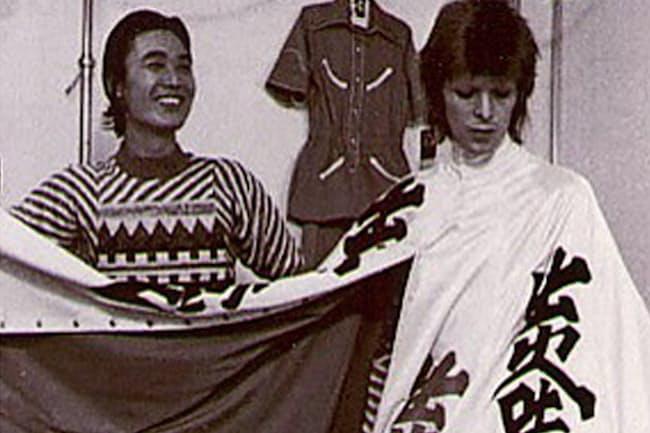 英ロックスター、デビッド・ボウイ(右)の舞台衣装をチェックする山本寛斎さん。「出火吐暴威(デビッド・ボウイ)」の当て字が見える(1973年、撮影は鋤田正義さん)
