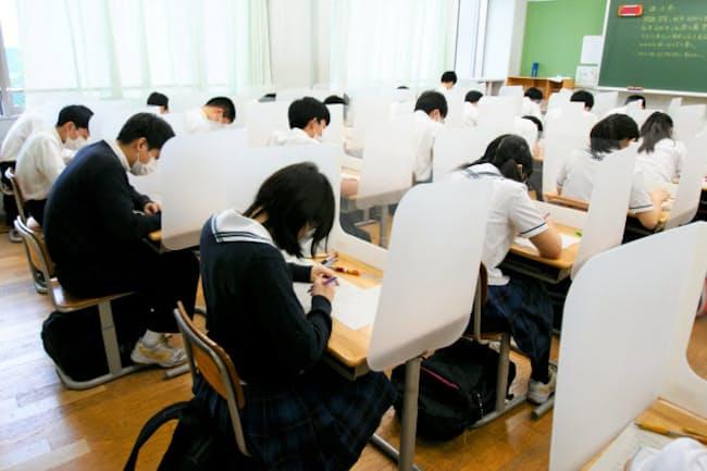 栄東中学校(さいたま市)では、授業でも使うパーテーションで受験生の間を仕切り、感染防止対策に努める