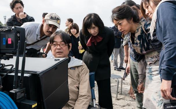 映画ロケの現場でモニターをチェックする本木克英監督(左から3人目)と主役の井上真央さん(右から2人目)(c)2021「大コメ騒動」製作委員会