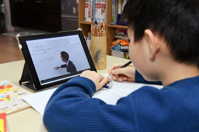 小中学生に1人1台の情報端末が配布される(学習塾の動画を自宅で勉強する小学生、2020年4月)