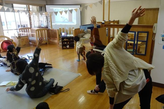 ズームで講師の動きを見ながらヨガを楽しむ親子(1月下旬、東京都港区の子育てひろば「あい・ぽーと」)