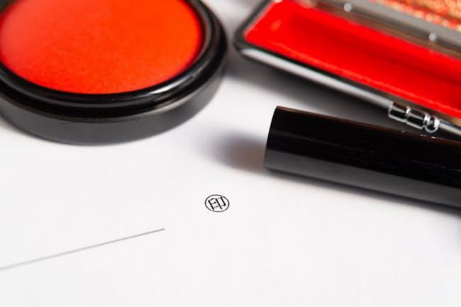 メイ氏は押印の前に書類を入念にチェックするという(写真はイメージ) =PIXTA