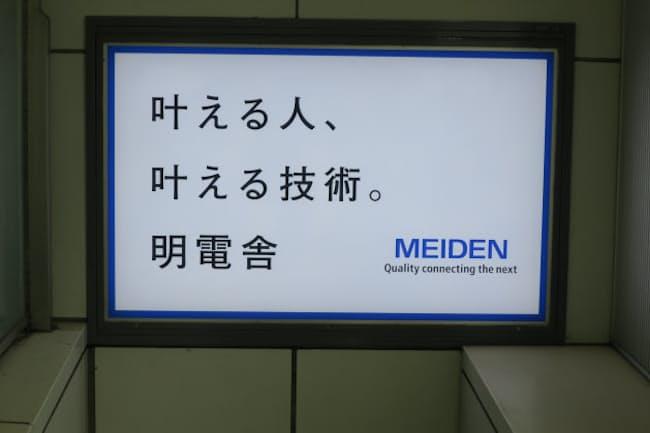 明電舎本社近くのJR大崎駅エスカレーターの広告(東京・品川)